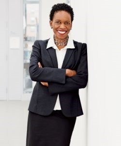 Woman in a black buisness suit with arms crossed standing against a wall and smiling