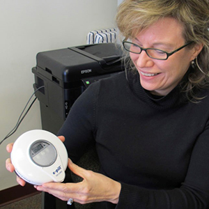 Woman with eyeglasses and black sweater smiling down at a round-shaped, electronic device she's holding