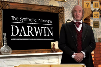 Still shot of a virtual Charles Darwin standing by a chalkboard that reads The Synthetic Review: Darwin and waiting for the app user to make their selection.