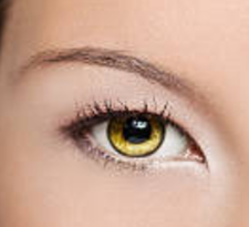 Close-up photo of the amber-colored eye of a young woman.