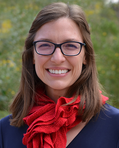 Profile photo of Melissa Wilson outside with red scarf, wearing glasses and smiling.