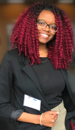 Photo of Charmaine Nganje, with curly red shoulder-length hair and eyeglasses, smiling..
