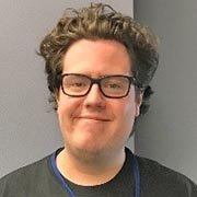 Profile picture of Eric Bock with curly hair and eyeglasses, smiling.