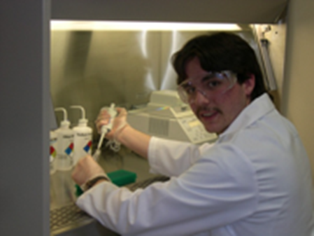 Caleb Marceau using a pipette to prepare specimens under a vent hood.