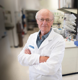 Vern Schramm in his lab, dressed in a white lab coat, standing with his arms folded across his chest.