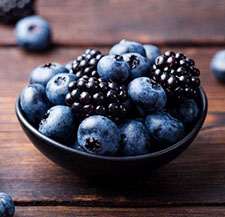 Blueberries and blackberries in a bowl and scattered on a wooden table.