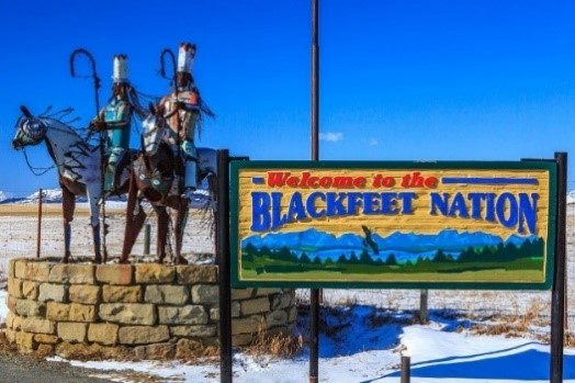 "A sign that says ""Welcome to the Blackfeet Nation"" next to a sculpture of two American Indians on horseback under a blue sky."