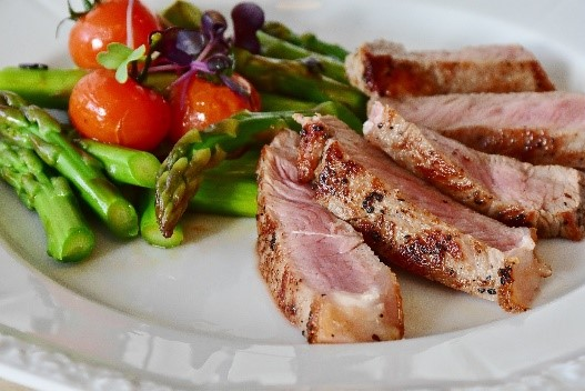 A plate with sliced meat, asparagus, and tomatoes.