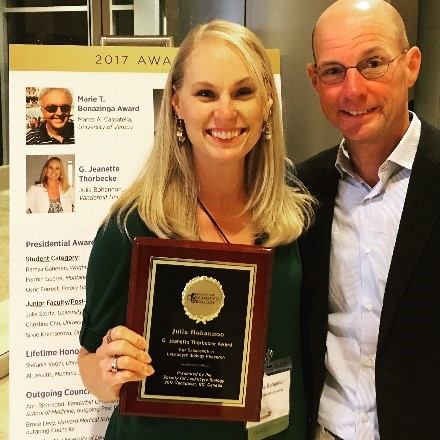 Dr. Bohannon holding an award plaque and standing next to Dr. Sherwood.